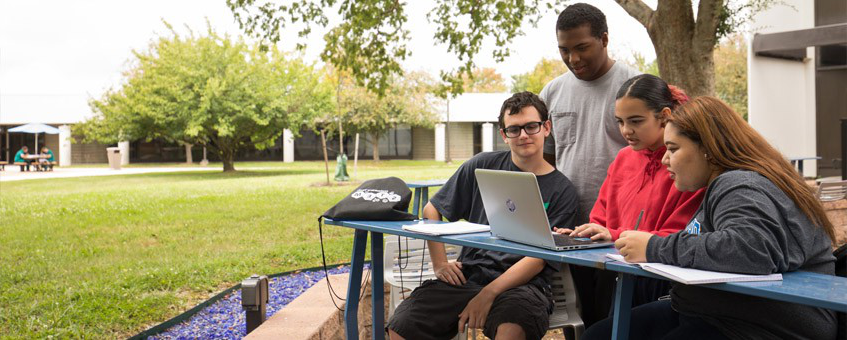 Students review coursework outside at a student lounge area.
