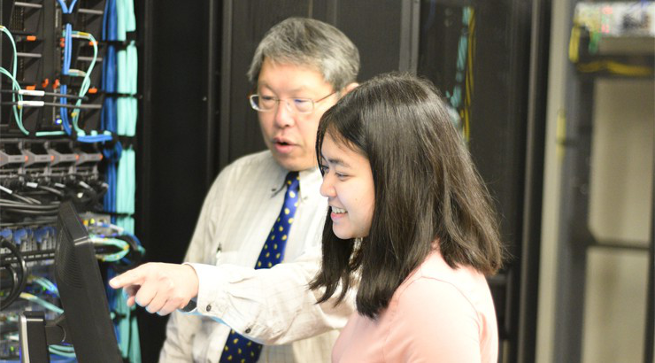 ITN Department Chair Tommy Lu pointing to a computer screen that student Katina Thongvong is looking at