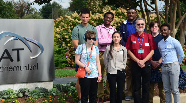 A group of students and instructors standing in front of the TA Instruments sign