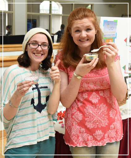 Two students holding spoons and small cups
